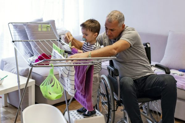 Photo of mature father on wheelchair having fun at home with his two years old son. Man hangs up laundry, to dry clothes. Father performs home duties, hangs up the child's clothes. Man in the role of a woman at home. A man in the role of a housewife.