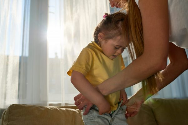 Concentrated little girl with downs syndrome tucking in tshirt while mother assisting her