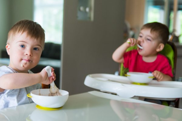 Down's syndrome sweet boy eating breakfast. He has blue eyes and blond hair. He is sitting at the table in the dining room with his 2 years old brother.  They wear pyjama short and t-shirts. The color and horizontal Photo was taken in Quebec Canada.