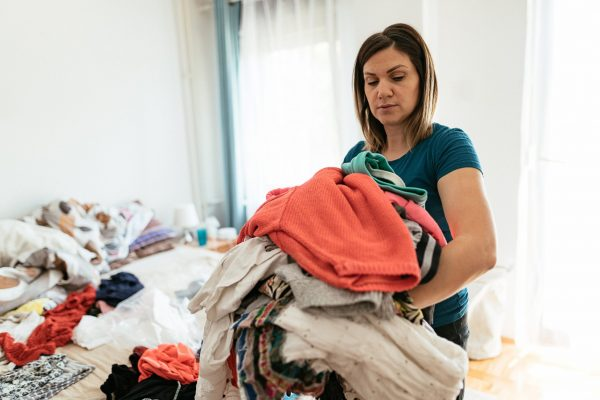Woman working at home, cleaning the floors, washing the laundry and cleaning up the mess in the closet during quarantine