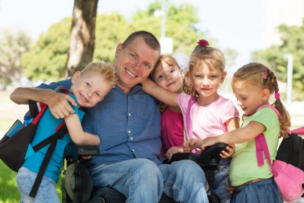 Disabled father with children having fun at the park