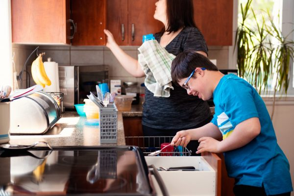 Mother helping her son of 12 years old with Down Syndrome in daily lives emptying the dishwasher. SHe is proud of his beautiful son. The little boy wear eyeglasses. Photo was taken in Quebec Canada.