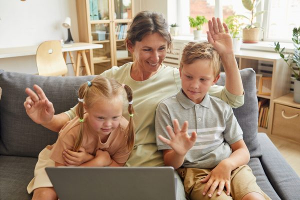 Portrait of happy family with special needs child waving at camera while enjoying video chat with relatives